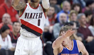 Portland Trail Blazers guard Damian Lillard shoots next to New York Knicks guard Ron Baker during the second half of an NBA basketball game in Portland, Ore., Thursday, March 23, 2017. (AP Photo/Craig Mitchelldyer)
