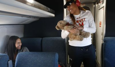 Maryland forwards Aja Ellison, left, and Kiah Gillespie joke about whether Gillespie's good luck teddy bear Sirr needs a bath, as the team rode an Amtrak Regional train from Baltimore to Stamford, Conn., Thursday, March 23, 2017. Only two of the team's players had ever taken a train, so coach Brenda Frese decided to take the train instead of a bus to the NCAA women's college basketball tournament Bridgeport Regional. (AP Photo/Kathy Willens)
