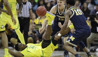 Oregon guard Dylan Ennis, left, fights for a loose ball with Michigan's Derrick Walton Jr. (10) and Moritz Wagner (13) during the first half of a regional semifinal of the NCAA men's college basketball tournament, Thursday, March 23, 2017, in Kansas City, Mo. (AP Photo/Charlie Riedel)