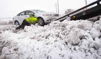 Tow truck operator Scott Klaproth pulls a vehicle out of deep snow on Friday, March 24, 2017 in Colorado Springs, Colo., Friday, March 24, 2017.  Blowing snow, low visibility and vehicles sliding off the road initially shut down about 400 miles of roads in southern and eastern Colorado Friday.  (Mark Reis/The Gazette via AP)