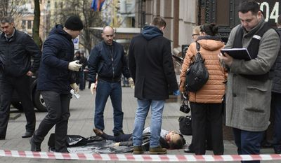 """EDS NOTE: GRAFIC CONTENT Forensic experts and police officers work at the place of killing of former Russian lawmaker Denis Voronenkov in Kiev, Ukraine, Thursday, March 23, 2017. Denis Voronenkov was shot and killed in Kiev Thursday in what the Ukrainian president described as an """"act of state terrorism"""" by Russia, an accusation the Kremlin quickly rejected. Voronenkov, who testified to Ukrainian investigators and criticized Russian policies after his move to Kiev last fall, was shot dead by an unidentified gunman. (AP Photo/Andrew Kravchenko)"""