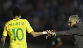 Brazil's Neymar, left, is congratulated by his coach Tite, after he scored against Uruguay during a 2018 World Cup qualifying soccer match in Montevideo, Uruguay, Thursday, March. 23, 2017. Brazil won the match 4-1. (AP Photo/Natacha Pisarenko)