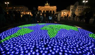 A globe illuminated with led-lights by activists of the World Wide Fund For Nature (WWF) in front of the Brandenburg Gate to mark Earth Hour, in Berlin, Saturday, March 25, 2017. (AP Photo/Markus Schreiber) ** FILE **