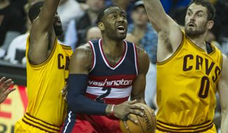 Washington Wizards' John Wall (2) drives past Cleveland Cavaliers' Tristan Thompson, left and Kevin Love during the first half of an NBA basketball game in Cleveland, Saturday, March 25, 2017. (AP Photo/Phil Long)