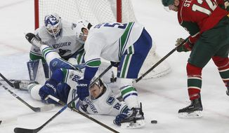 Vancouver Canucks' Nikita Tryamkin (88), of Russia, helps goalie Richard Bachman defend the net from a prone position on the ice against Minnesota Wild's Eric Staal, right, during the second period of an NHL hockey game Saturday, March 25, 2017, in St. Paul, Minn. Helping on the play is Luca Sbisa (5).  (AP Photo/Jim Mone)