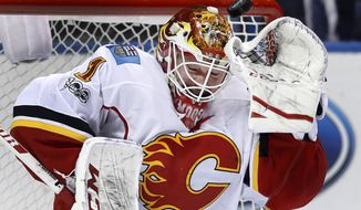 A puck sails over the head of Calgary Flames goalie Brian Elliott during the second period of an NHL hockey game against the St. Louis Blues, Saturday, March 25, 2017, in St. Louis. (AP Photo/Jeff Roberson)