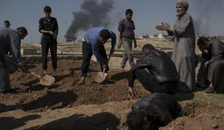 Relatives and friends bury the body of Khadeer Hassan, who was killed during fighting between Iraqi security forces and Islamic State militants, on the western side of Mosul, Iraq, Saturday, March 25, 2017. (AP Photo/Felipe Dana)