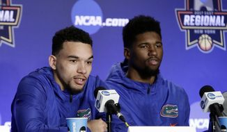 Florida's Chris Chiozza, left, speaks during a news conference as teammate Kevarrius Hayes, right, listens Saturday, March 25, 2017, in New York. Florida plays South Carolina in the East Regional final at the NCAA college basketball tournament . (AP Photo/Frank Franklin II)
