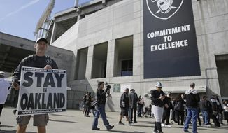 John P. Kelleher holds up a sign outside the Oakland Coliseum before the start of a rally to keep the Oakland Raiders from moving Saturday, March 25, 2017, in Oakland, Calif. NFL owners are expected to vote on the team's possible relocation to Las Vegas on Monday or Tuesday at their meeting in Phoenix. (AP Photo/Eric Risberg)