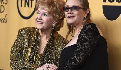 FILE - In this Jan. 25, 2015 file photo, Debbie Reynolds, winner of the Screen Actors Guild lifetime award, left, and Carrie Fisher pose in the press room at the 21st annual Screen Actors Guild Awards in Los Angeles. The mother-daughter actresses will be honored at a public memorial on Saturday, March 25, 2017, at the storied Hollywood Hills cemetery where both have been laid to rest. Fisher and Reynolds died one day apart in late December 2016. (Photo by Jordan Strauss/Invision/AP, File)