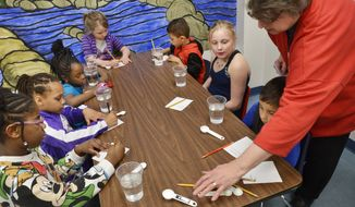 Library assistant Sharon Vodraska, at right, helps participants prepare an experiment to test how much salt it takes to float an egg in a glass of water during the Sensory Science program in the Children's/Youth Services room at the Marion Public Library in Marion, Ind., on Thursday, March 23, 2017.  (Jeff Morehead /The Chronicle-Tribune via AP)