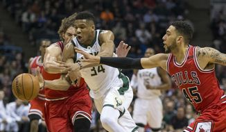 Chicago Bulls' Robin Lopez, left, and Denzel Valentine try to stop Milwaukee Bucks' Giannis Antetokounmpo during the first half of an NBA basketball game, Sunday, March 26, 2017, in Milwaukee. (AP Photo/Tom Lynn)
