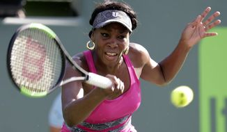 Venus Williams hits a return to Patricia Maria Tig during the Miami Open tennis tournament, Sunday, March 26, 2017, in Key Biscayne, Fla. (AP Photo/Lynne Sladky)