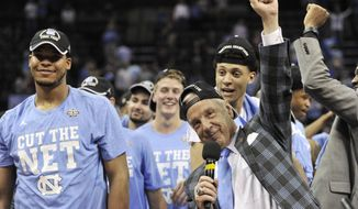 North Carolina head coach Roy Williams, right, celebrates with his team after beating Kentucky 75-73 in the South Regional final game in the NCAA college basketball tournament Sunday, March 26, 2017, in Memphis, Tenn. (AP Photo/Brandon Dill)