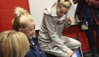 Connecticut guard Katie Lou Samuelson watches a computer in the team's locker room in Bridgeport, Conn., as her sister Karlie's Stanford team takes on Notre Dame in the NCAA Tournament's Lexington regional on March 26, 2017. (AP Photo/Pat Eaton-Robb)