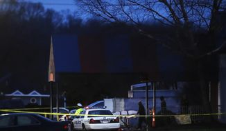 A body is removed as police operate at a crime scene outside the Cameo club after a fatal shooting, Sunday, March 26, 2017, in Cincinnati. (AP Photo/John Minchillo)