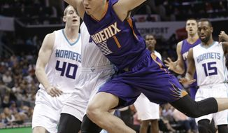Phoenix Suns' Devin Booker (1) is fouled as he drives past Charlotte Hornets' Michael Kidd-Gilchrist (14) in the first half of an NBA basketball game in Charlotte, N.C., Sunday, March 26, 2017. (AP Photo/Chuck Burton)