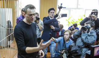 Russian opposition leader Alexei Navalny, foreground,  speaks to press in a court room in Moscow, Russia, Monday, March 27, 2017. Russian opposition leader Alexei Navalny is making a court appearance Monday, a day after being detained at a major opposition rally on Sunday. (AP Photo/Denis Tyrin)