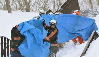 Rescuers carry the people who got injured in an avalanche at a ski resort in Nasu, Tochigi prefecture, Monday,  March 27, 2017. Authorities said six Japanese high school students have been found unconscious after they were caught in the avalanche Monday morning. (Kyodo News via AP)