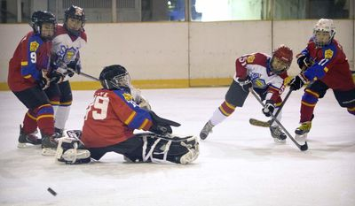 In this Saturday, Feb. 18, 2017, photo, a Chinese player takes a shot on goal during a youth ice hockey tournament in Beijing. With the 2022 Winter Olympics taking place in Beijing, China is eager to step up its game and the NHL can't help but be intrigued by the potential of a new market with 1.3 billion people who might take to hockey like they did basketball. (AP Photo/Mark Schiefelbein)