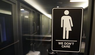 "This Thursday, May 12, 2016, file photo, shows a sign outside a restroom at 21c Museum Hotel in Durham, N.C. The Associated Press has determined that North Carolina's law limiting LGBT protections will cost the state more than $3 billion in lost business over a dozen years. That's despite Republican assurances that the ""bathroom bill"" isn't hurting the economy. (AP Photo/Gerry Broome, File)"