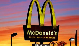 FILE - In this Saturday, Oct. 10, 2015, file photo, the sun sets behind a McDonald's in Ebensburg, Pa. A 94-year-old McDonald's worker in Evansville, Indiana, was honored for 44 years at the company on March 23, 2017. (AP Photo/Gene J. Puskar, File)