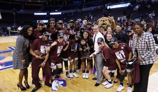 Mississippi State players and coaches celebrate with the championship trophy after a regional final of the NCAA women's college basketball tournament against Baylor, Sunday, March 26, 2017, in Oklahoma City. Mississippi State won 94-85. (AP Photo/Alonzo Adams)