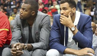 Injured Atlanta Hawks forward Paul Millsap, left, and guard Thabo Sefolosha watch from the bench as the Hawks fall 107-92 to the Brooklyn Nets in an NBA basketball game Sunday, March 26, 2017, in Atlanta. It is the Hawks seventh consecutive loss and the fifth consecutive game Millsap has missed. (Curtis Compton/Atlanta Journal-Constitution via AP)