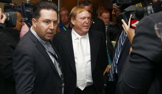 Oakland Raiders owner Mark Davis, center, emerges from a news conference at the NFL football annual meetings after owners approved the move of the Raiders to Las Vegas, Monday, March 27, 2017, in Phoenix. (AP Photo/Ross D. Franklin)