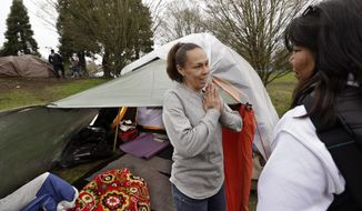 In this photo taken Thursday, March 23, 2017, Sheryl, left, a homeless woman who declined to give her last name, talks with outreach worker Brenda Frazier, as part of a new team of outreach workers and police officers that go out and connect homeless people to services in Seattle. Sheryl said she has lived in a tent in a greenbelt near Interstate Highway 90 for about six months. (AP Photo/Elaine Thompson)