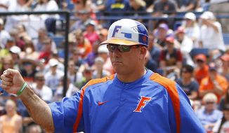 FILE - In this May 31, 2015, file photo, Florida's head coach Tim Walton gestures to one of his players in the fourth inning during an NCAA Women's College World Series game against Auburn in Oklahoma City. Florida softball coach Tim Walton was involved in an altercation with Auburn shortstop Haley Fagan on Monday night, March 27, 2017, after Walton gave Fagan a slight push during postgame handshakes. (AP Photo/Alonzo Adams, FIle) **FILE**