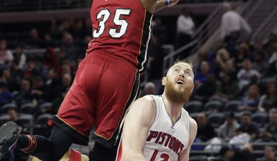 Miami Heat forward Willie Reed (35) towers over Detroit Pistons center Aron Baynes (12) during the first half of an NBA basketball game, Tuesday, March 28, 2017, in Auburn Hills, Mich. (AP Photo/Carlos Osorio)