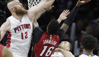 Detroit Pistons center Aron Baynes (12) attempts a block on Miami Heat forward James Johnson (16) during the first half of an NBA basketball game, Tuesday, March 28, 2017, in Auburn Hills, Mich. (AP Photo/Carlos Osorio)