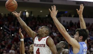 FILE - In this Feb. 15, 2017, file photo, North Carolina State's Dennis Smith Jr. (4) shoots against North Carolina during the the first half of an NCAA college basketball game in Raleigh, N.C. Smith, the Atlantic Coast Conference freshman of the year, is headed to the NBA after one season with the Wolfpack. (AP Photo/Gerry Broome, File)