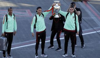 Portugal's Cristiano Ronaldo and Pepe, right, show off the Euro 2016 European soccer championship trophy as they arrive at the Madeira airport outside Funchal, the capital of Madeira island, Portugal, Monday, March 27 2017.  At left is teammate Bruno Alves. Ronaldo will play in his hometown of Funchal Tuesday when Portugal faces Sweden in a friendly soccer match. (AP Photo/Armando Franca)