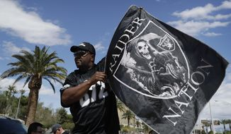Ken Mclin holds up a Raiders banner Monday, March 27, 2017, in Las Vegas. NFL team owners approved the move of the Raiders to Las Vegas in a vote at an NFL football annual meeting in Phoenix. (AP Photo/John Locher)