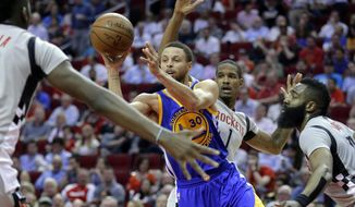 Golden State Warriors' Stephen Curry (30) dishes the ball between Houston Rockets' Clint Capela, Trevor Ariza (1) and James Harden (13) in the first half of an NBA basketball game in Houston, Sunday, March 28, 2017. (AP Photo/Michael Wyke)