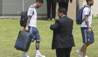 """Argentina's Lionel Messi, left, walks to a waiting bus in Santa Cruz de la Sierra, Bolivia, Tuesday, March 28, 2017. Messi has been banned from Argentina's next four World Cup qualifiers, starting with Tuesday's game in Bolivia, for """"having directed insulting words at an assistant referee"""" during a home qualifier against Chile last Thursday, FIFA said hours before kickoff in La Paz. (AP Photo)"""