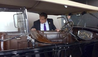 In this March 28, 2017 photo, New York Gov. Andrew Cuomo looks over the Packard Phaeton once used by Franklin D. Roosevelt when he was governor of New York, at the State Museum in Albany. The car, used by FDR from 1929 until his election as president in November 1932, is headed off to an antique vehicle expert in Connecticut for some repairs. Cuomo, who plans to use the car for ceremonial occasions, such as the scheduled 2018 opening of the new Tappan Zee Bridge, says the repairs will not alter the paint, wheels or upholstery, and will instead focus on basic preservation. (AP Photo/Anna Gronewold)