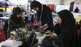 FILE - In this April 6, 2016, file photo, Iranian students prepare their robots during the international robotics competition, RoboCup Iran Open 2016, in Tehran, Iran. Universities in the U.S. say President Donald Trump's revised travel ban would block hundreds of graduate students who play key roles in research. Twenty-five of America's largest universities told The Associated Press they've sent acceptance letters to more than 500 students from the six banned countries for next fall, mostly from Iran, who are known for their strength in engineering and sciences. (AP Photo/Vahid Salemi)