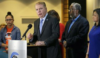 FILE - In this Nov. 9, 2016, file photo, Seattle Mayor Ed Murray, second left, speaks at a post-election event of elected officials and community leaders at City Hall in Seattle. On Wednesday, March 29, 2017, Murray announced that Seattle is suing President Donald Trump over his executive order that threatens to withhold federal funds from communities that refuse to cooperate with efforts to find and deport immigrants in the country illegally. (AP Photo/Elaine Thompson, File)