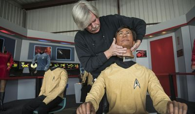 """In this Saturday, March 25, 2017 photo, Steve Greenthal places the wax head of Star Trek character Sulu on its body at a hangar in the Fullerton Airport in Fullerton, Calif. Greenthal and friend Chris Liebl purchased the group of figures more than a decade ago from the old Movieland Wax Museum in Buena Park. The Hollywood Science Fiction Museum recently took possession of wax figures of all seven crew members from the 1960s """"Star Trek"""" TV series. (Nick Agro/The Orange County Register via AP)"""