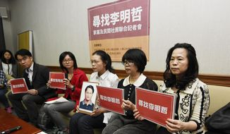"In this photo taken Friday, March 24, 2017, Lee Ching-yu, third from right holds up a photo of her missing husband and Taiwanese pro-democracy activist Lee Ming-che during a press conference with other representatives of non-governmental organizations calling for help to find his whereabouts in Taipei, Taiwan. Lee believed to be in Chinese custody may have attracted the attention of China's security services after he used the social media site WeChat to discuss China-Taiwan relations, a colleague said Tuesday. Chinese characters on cards read ""Finding Lee Ming-che"" (AP Photo)"