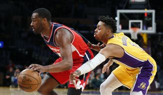 Washington Wizards guard John Wall, left, takes the ball past Los Angeles Lakers guard D'Angelo Russell, right, on the way to making a dunk during the first half of an NBA basketball game, Tuesday, March 28, 2017, in Los Angeles. (AP Photo/Danny Moloshok)