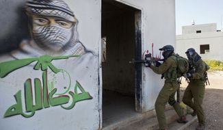 "In this Wednesday, March 29, 2017 photo, Israeli soldiers train with paintball guns during a drill at an Army base near Elyakim, Israel. Between myriad concrete buildings with Arabic graffiti that are designed to simulate a typical Lebanese village, dozens of Israeli officers are gearing up for their next battle with Hezbollah guerrillas. The drill at a base in northern Israel takes on added significance in the wake of rising tensions between the old adversaries. Arabic reads, ""Hezbollah."" (AP Photo/Sebastian Scheiner)"