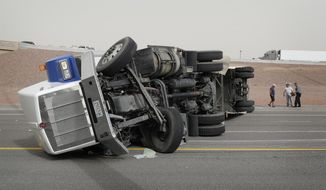 A tractor-trailer lies on its side on Interstate 15, Thursday, March 30, 2017, south of Las Vegas. The Nevada Highway Patrol says high winds caused the rollover of the tractor-trailer that was blocking all the lanes of northbound Interstate 15 into Las Vegas. (AP Photo/John Locher)