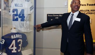 """FILE - In this April 9, 2015, file photo, former Dallas Cowboys player Everson Walls stands near his jersey before the 2015 Texas Sports Hall of Fame induction class news conference in Waco, Texas. Walls doesn't want to talk about The Catch, and not just because he wasn't the one catching the ball.  """"It's not fresh anymore,'' Walls said. ``I can't make it any more than it was.'' He does want to talk about Dwight Clark, who leaped high over him that fateful day at Candlestick Park in a play that will live in NFL lore. (Rod Aydelotte/Waco Tribune-Herald via AP, File)"""