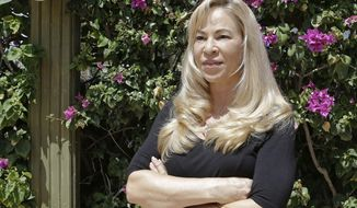 In this Tuesday, March 28, 2017 photo, Sherri Simpson poses for a photo in Fort Lauderdale, Fla. President Donald Trump's $25 million settlement of a class-action lawsuit that alleged fraud at his now-defunct Trump University may be put on hold because Simpson, former student in Florida, wants a full refund plus interest and an apology (AP Photo/Alan Diaz)