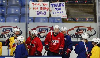 United States teammates practice with fans holding support signs in preparation for the IIHF Women's World Championship hockey tournament, Thursday, March 30, 2017, in Plymouth, Mich. USA Hockey and the women's national team agreed to a contract Tuesday night that ended a wage dispute. (AP Photo/Paul Sancya)
