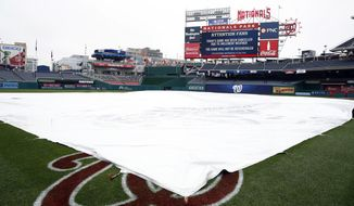 A tarp covers the field as it is announced the Washington Nationals-Boston Red Sox exhibition baseball game was canceled at Nationals Park, Friday, March 31, 2017, in Washington. (AP Photo/Alex Brandon)